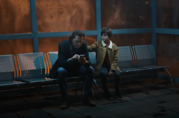 man with distracted by phone at busstop with boy